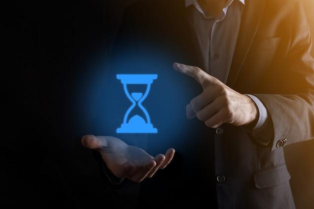Homem empresário detém ícone de ampulhetas na mão. o tempo acabou. um lembrete para a ação. conceito de negócios. elementos de design.
