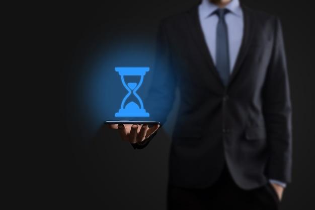 Homem empresário detém ícone de ampulhetas na mão. o tempo expira. um lembrete para a ação. conceito de negócios. elementos de design.