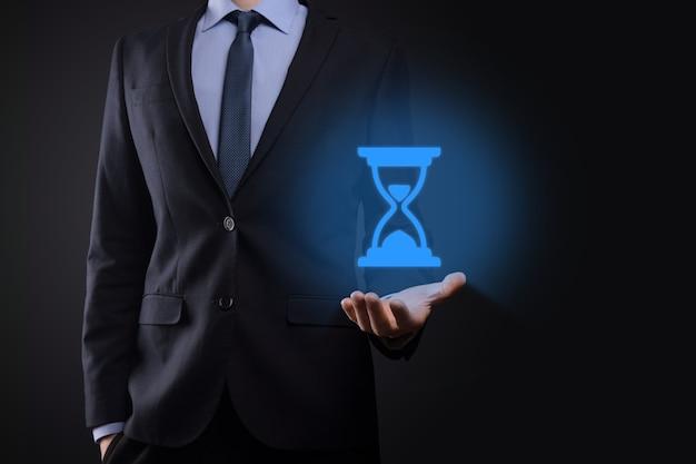 Homem empresário detém ícone de ampulhetas na mão. o tempo expira