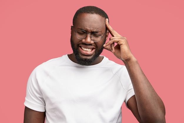 Homem empresário estressado enfrenta crise financeira, tem olhar infeliz, mantém o dedo da frente na cabeça, cerra os dentes