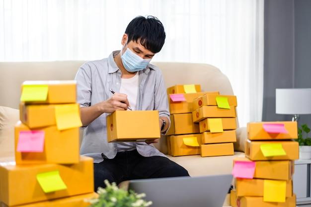 Homem empresário prepara caixa de encomendas para entrega ao cliente no escritório residencial, ele usa máscara facial para proteção de pandemia de coronavírus