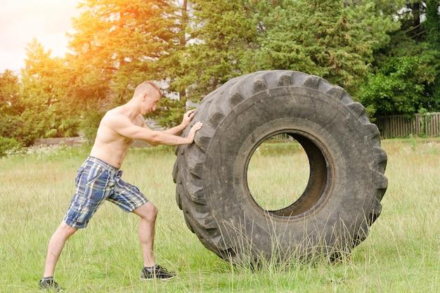 Homem empurra um pneu grande. treino de rua