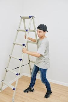 Homem empurrando escada para parede
