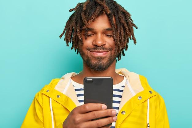 Homem encantado de pele escura, tem dreads, olha positivamente para smartphone, vê fotos, veste capa de chuva amarela