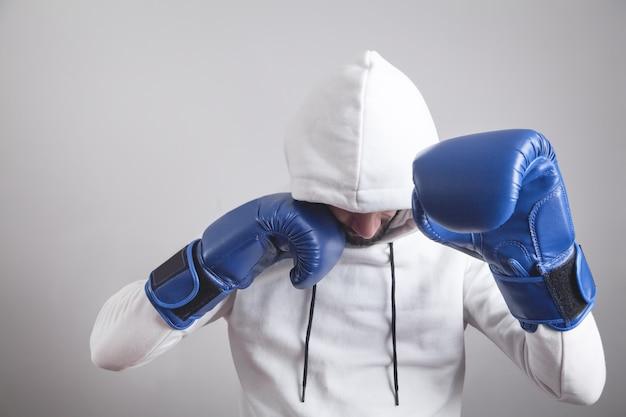 Homem encapuzado com luvas de boxe.