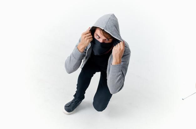 Homem encapuzado mascarado escondendo roubo de rosto