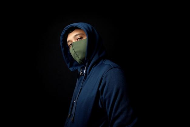 Homem encapuzado parado no escuro