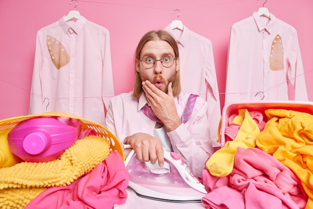 Homem encara as roupas de ferros chocadas cercadas por pilhas de roupas e posa em rosa
