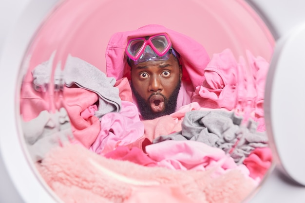 Homem encara olhos esbugalhados para a câmera coberta com uma pilha de roupas sujas poses através do tambor da máquina de lavar cheio de roupas sujas usa máscara de mergulho