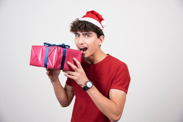 Homem encaracolado com chapéu de papai noel, posando com caixa de presente.