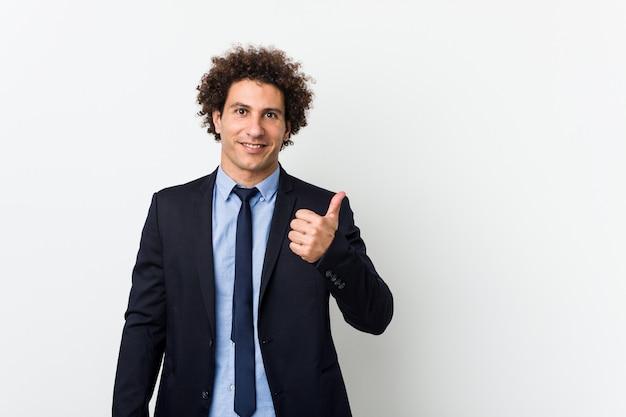 Homem encaracolado de negócios jovem sorrindo e levantando o polegar