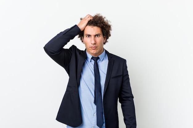 Homem encaracolado do negócio novo contra a parede branca cansado e muito sonolento mantendo a mão na cabeça.