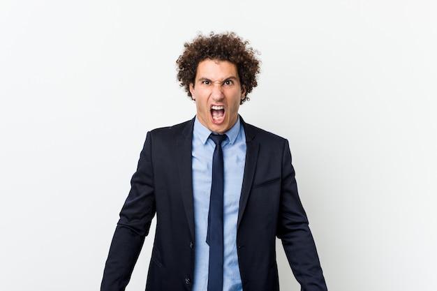Homem encaracolado do negócio novo contra a parede branca que grita muito irritado e agressivo.