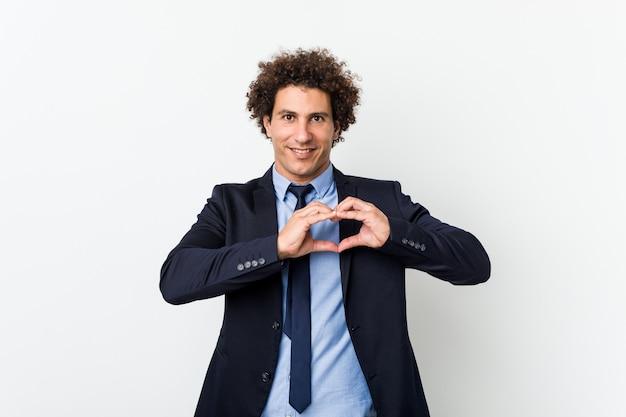 Homem encaracolado do negócio novo contra a parede branca que sorri e que mostra uma forma do coração com mãos.