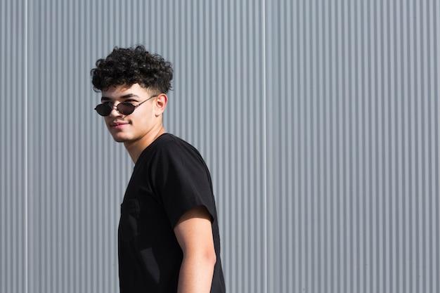 Homem encaracolado em óculos de sol, olhando para longe na cerca cinza