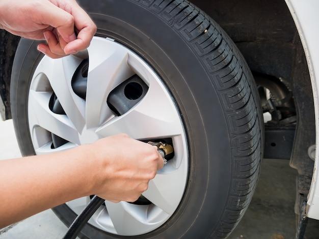Homem enchendo a pressão do ar no pneu do carro de perto