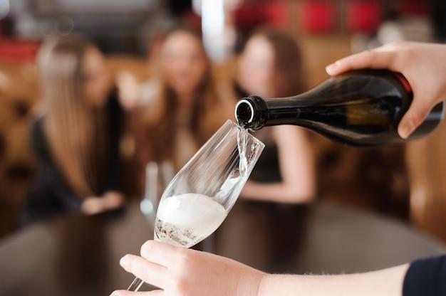Homem enchendo taças de champanhe para três belas moças em restaurante