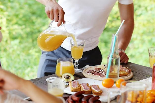 Homem enchendo um copo com suco de laranja