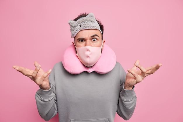 Homem encolhe os ombros parece com expressão indignada e usa máscara protetora de travesseiro de pescoço vendada