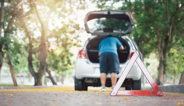 Homem encontra ferramentas no carro para conserto após uma pane na rua com um triângulo em primeiro plano