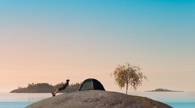 Homem encontra o amanhecer em uma pequena ilha de granito. as mãos atrás da cabeça