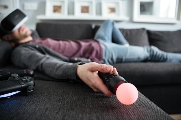 Homem encontra-se no sofá usando óculos de realidade virtual, segurando o joystick.