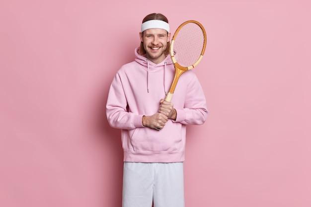 Homem energético feliz e esportivo segurando raquete de tênis gosta de jogar o jogo favorito tem vida ativa usa camiseta com faixa na cabeça e shorts gosta de um ótimo dia para jogar