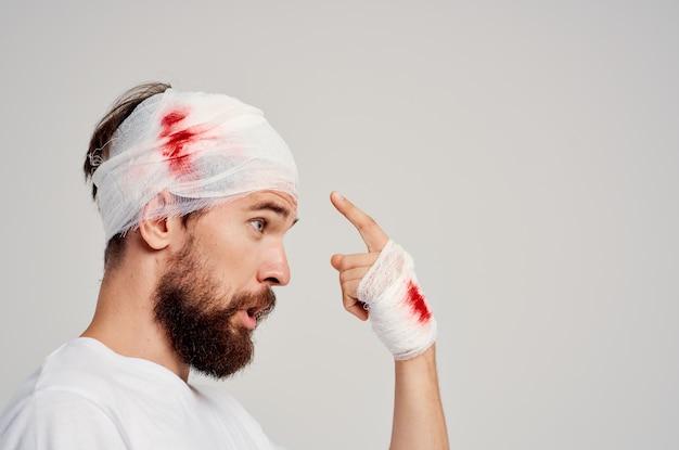 Homem enfaixado cabeça e mão com fundo isolado de sangue
