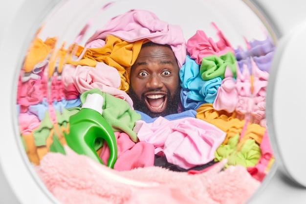 Homem enfia a cabeça em poses de roupas multicoloridas no tambor da máquina de lavar com uma garrafa de detergente