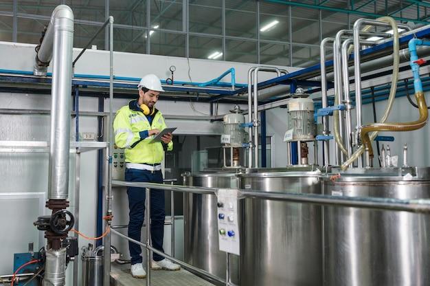 Homem engenheiro caucasiano de uniforme caminhando para verificar os tanques da caldeira com tubulação de líquido na fábrica de processamento de bebidas