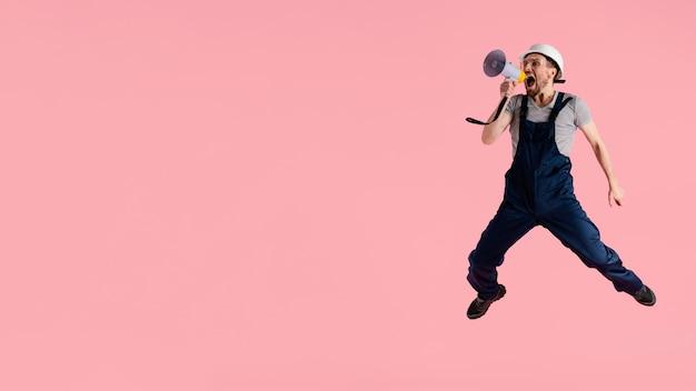 Homem engenheiro de retratos pulando com megafone