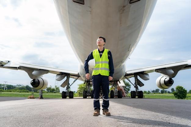 Homem engenheiro manutenção avião segurando capacete branco na frente do avião de reparos