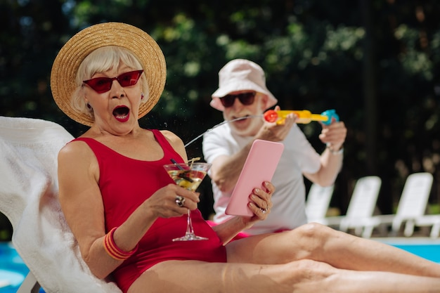 Homem engraçado borrifando água fria em sua esposa madura e elegante usando óculos de sol vermelhos brilhantes