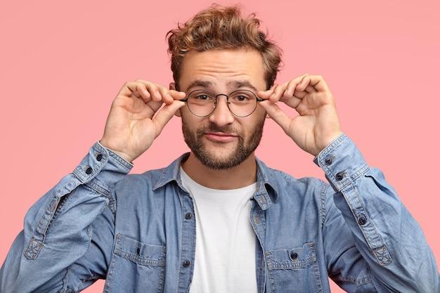 Homem engraçado com a barba por fazer tem barba espessa, mantém as duas mãos na borda dos óculos, tem olhar curioso enquanto ouve algo interessante