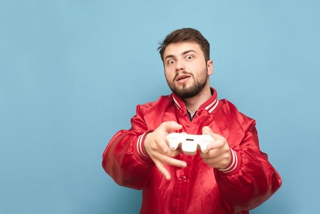 Homem engraçado com barba em pé no azul com um gamepad na mão e jogando videogame