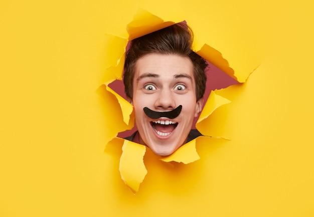 Homem engraçado com bigode olhando pelo buraco de papel rasgado