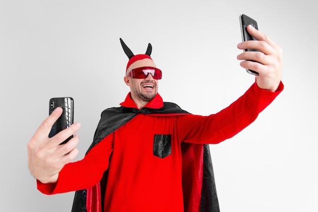 Homem engraçado com capa vermelha preta de halloween, óculos escuros e chapéu com chifres tirando selfie com smartphone