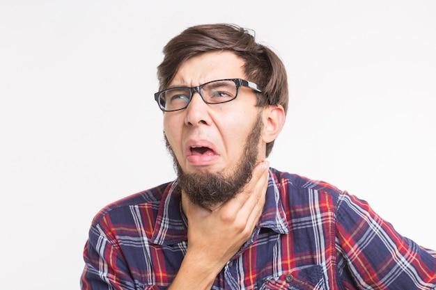 Homem engraçado com dor de garganta e tocando o pescoço isolado na superfície branca