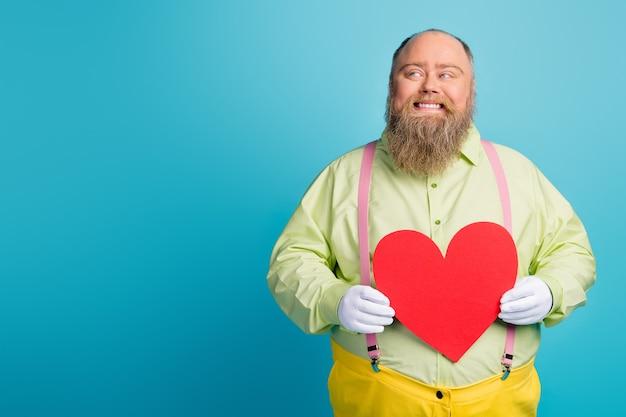 Homem engraçado com excesso de peso segurando coração de cartão de papel dos namorados no fundo azul do espaço vazio