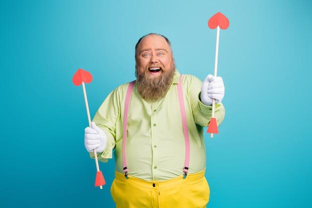 Homem engraçado com excesso de peso segurando setas em formato de coração sobre fundo azul
