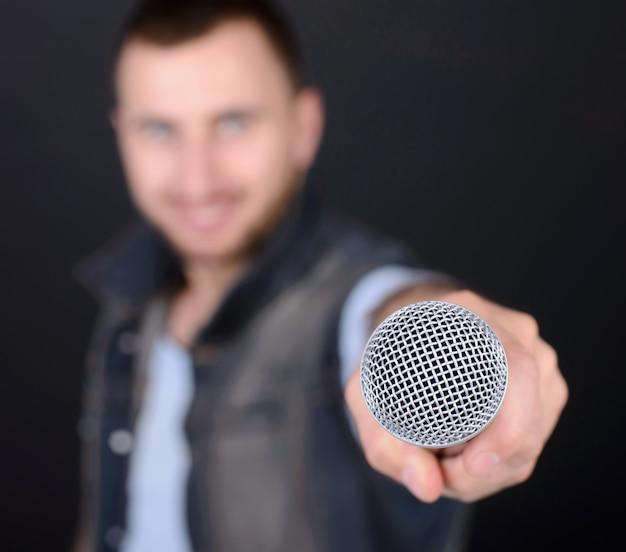 Homem engraçado com microfone cantando karaokê.