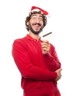 Homem engraçado com um cartão de crédito e um chapéu de santa