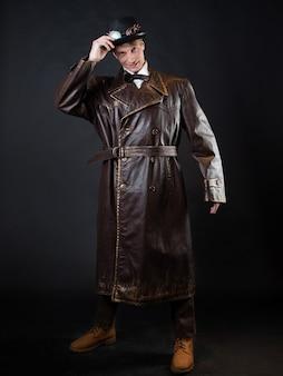Homem engraçado com um casaco de couro ridículo e uma cartola, roupas estilo vintage, foto em um fundo preto