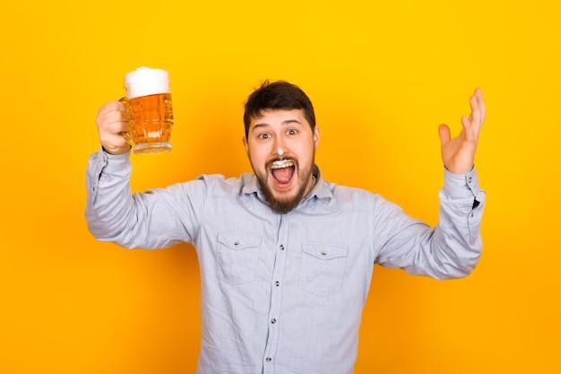 Homem engraçado com um copo de cerveja e espuma no bigode e nariz em uma parede amarela, conceito de festa