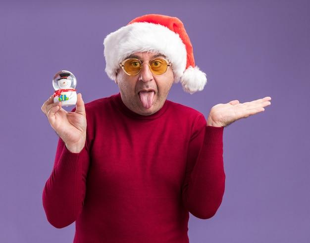Homem engraçado de meia-idade usando chapéu de papai noel de natal em óculos amarelos segurando globo de neve de natal com a língua para fora com o braço levantado em pé sobre fundo roxo