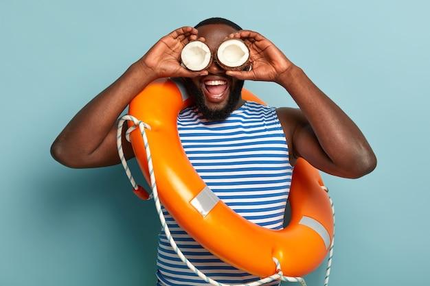 Homem engraçado de pele escura se diverte sozinho, segura cocos nos olhos e tenta olhar para longe da praia