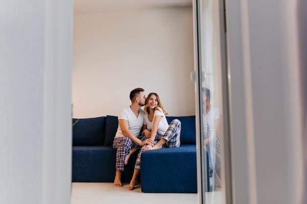 Homem engraçado descalço de pijama beijando sua esposa. retrato interior de casal preguiçoso, aproveitando a manhã.