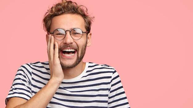 Homem engraçado e encaracolado ri alegremente, toca bochechas, assiste a programas interessantes, vestido com uma camiseta listrada casual, fica encostado na parede rosa.