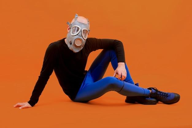 Homem engraçado e estranho no respirador posando sobre fundo laranja