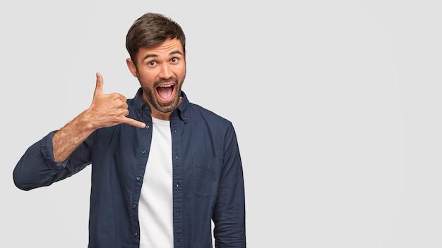 Homem engraçado e feliz mantém a mão perto da orelha, faz gesto de chamada, finge estar falando com alguém, mantém a boca bem aberta, vestido com uma camisa da moda, isolado sobre uma parede branca, espaço livre à parte.